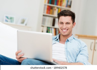 Happy relaxed young man with a friendly smile sitting on a sofa at home working on his laptop computer
