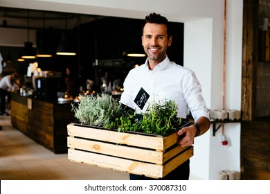 Happy restaurant manager holding box with fresh spices