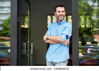 Happy restaurant owner standing at entrance looking away