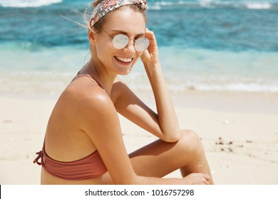 Happy restful smiling female in dark glasses and swimwear, bathes in sun on hot sandy beach near beautiful blue sea or ocean, enjoys good summer day and sunshine. Recreation and holidays concept