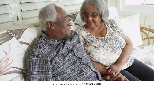 Happy retired black couple sitting on a couch