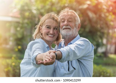 Happy retired couple dancing and relaxing in the park on sunny day