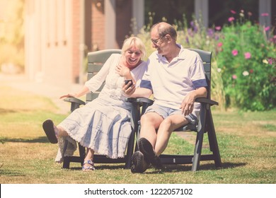 Happy retired couple sitting in the sunny garden, laughing together, looking on smartphone
