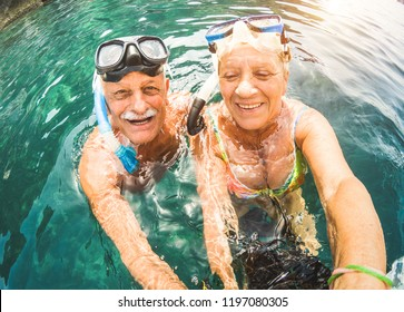 Happy retired couple taking selfie in tropical sea excursion with water camera and snorkel masks - Boat trip snorkeling in exotic scenarios - Active seniors and elderly travel concept around the world