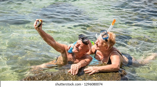 Happy retired couple taking selfie in tropical sea excursion with water camera and snorkel mask - Boat trip snorkeling in exotic scenarios - Elderly concept with active seniors traveling around world