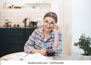 Happy retired lady with gray hair and round eyewear sitting at kitchen table writing down her ideas and thoughts in copybook, drinking morning coffee, looking at camera with joyful confident smile