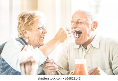 Happy retired senior couple in love enjoying bio icecream cup - Joyful elderly lifestyle concept - Wife feeding husband and having fun at bar cafe restaurant during evergreen vacation - Retro filter