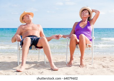 07a4fa39336ef1 happy retired senior couple sitting on the beach holding hands and enjoying  summer vacations