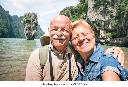 Happy retired senior couple taking travel selfie around world - Active elderly concept with people having fun together at James Bond Island in Thailand - Mature people lifestyle - Warm day filter