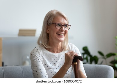 Happy retired woman in eyeglasses sitting on comfortable sofa, holding walking stick. Smiling pleasant older lady using cane during rehabilitation process. Medical insurance, healthcare concept.