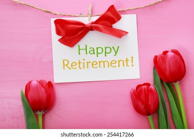 Happy Retirement card hanging with clothespins over red tulips and pink wooden board