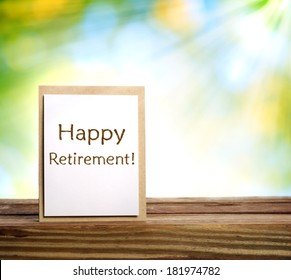Happy retirement card on wooden board over shiny green background