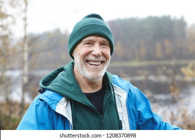 Happy retirement concept. Picture of joyful Caucasian unshaven senior male wearing green hat, hoodie and jacket looking at camera with cheerful broad smile, enjoying warm autumn morning outdoors