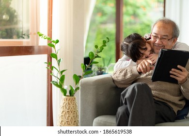 Happy retirement elderly man sitting on sofa at living room with granddaughter using digital tablet together. Multigenerational family with technology concept.