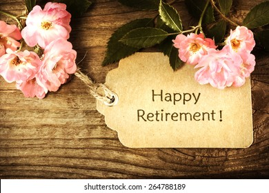 Happy Retirement message with small roses on rustic wooden table