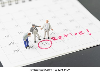 Happy retirement, wealth plan for life after retire from work concept, group of miniature happy senior old men standing with circle on white calendar with handwriting the word retire.