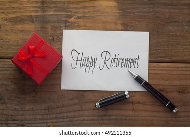 Happy Retirement written on paper with pen,red gift box and wooden background desk.