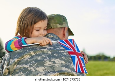Happy reunion of british soldier and his little daughter. Girl with british flag is embracing her father.