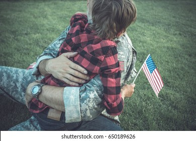 Happy reunion of soldier with family outdoors, detail, focus on hand with american flag. toned dark with vignette image, film effect