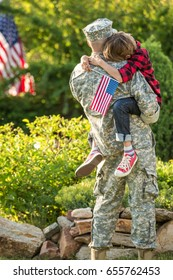Happy reunion of soldier with family outdoors, father hugs his son