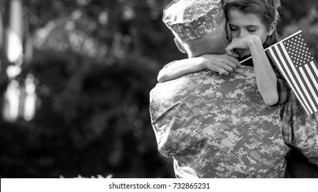 Happy reunion of soldier with family, son hug father. Black and white emotional portrait of american soldier father and his son