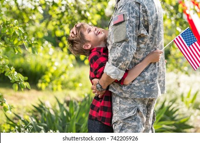 Happy reunion of soldier with family, son hug father