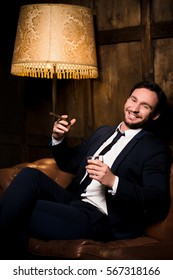 Happy rich businessman in men's club spending free time. Handsome man in business suit smoking cigar and drinking whiskey.