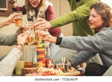 Happy rich friends celebrating with beer after skiing day in bar pub restaurant - Young people cheering in brewery chalet party - Friendship and holidays concept - Focus on left bottom hand
