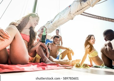 Happy rich friends having boat party in caribbean sea - Young people having fun drinking beer and listening music - Focus on five bottom guys faces - Soft desaturated contrast filter with back light