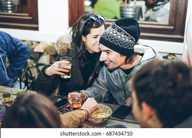Happy rich friends toasting beers at chalet pub restaurant in mountains on evening time - Young people having fun in winter vacation - Friendship concept - Soft focus on woman face - Warm filter