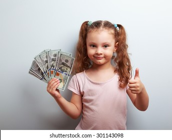 Happy rich kid girl holding money and showing thumb up sign on blue background with empty copy space