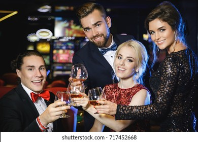 Happy and rich people celebrating their win after successful game in the casino