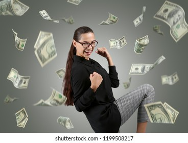 Happy rich woman with falling dollar banknotes on grey background