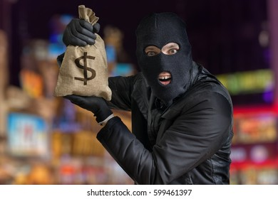 Happy robber is showing stolen bag full of money at night.