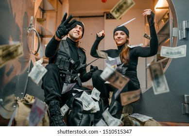 Happy robbers throwing money at the vault