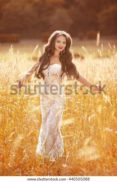 Happy Romantic bride in wedding dress enjoying on the Field in Sun Light at sunset Beauty Girl Outdoor Portrait.