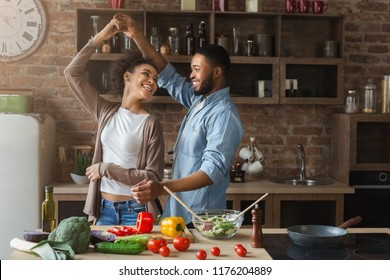 Happy romantic couple dancing in kitchen while cooking together