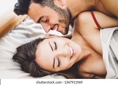 Happy romantic couple having sex - Young lovers during foreplay having tender and intimate moments in the bed - People, sexual, love and relationship concept