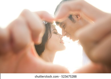 Happy romantic couple in love gesturing a heart with fingers