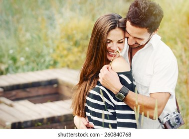 happy romantic couple in love and having fun with daisy at the lake outdoor in summer day, beauty of nature, harmony concept