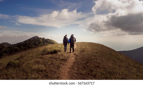 Happy romantic Couple Man and Woman, Travelers with backpack holding hands mountaineering, Travel Lifestyle and relationship love concept mountains landscape on background.