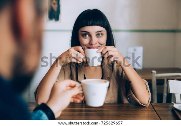 デートで幸せなロマンチックなカップル、ミルクで温かいコーヒーを飲み、恋人やパートナーを愛するように見え、ほほ笑み、目に輝く。早朝の家族の日課