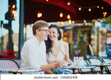 Happy romantic couple in Paris, drinking coffee in traditional Parisian outdoor cafe. Tourists spending their vacation in France