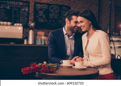 Happy romantic couple sitting in a cafe drinking coffee.