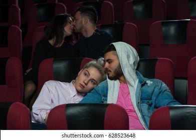 Happy romantic couples in movie theater