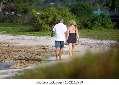 Happy romantic elderly couple enjoying a walk on the beach
