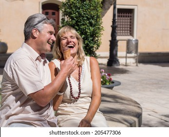 Happy romantic mature attractive middle-aged couple sitting on a stone wall in an urban square laughing at a good joke as they enjoy an ice cream in the summer heat