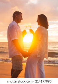 Happy Romantic Mature Couple Enjoying Glass of Champagne at Sunset on the Beach