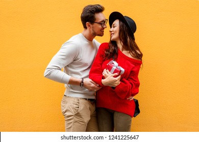 Happy romantic moment of two white people n love celebrating new year or Valentine's Day.  Long haired woman with gift box in hands laughing. Wearing trendy red knitted sweater. Yellow background.