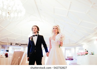 Happy romantic newlyweds holding hands in empty wedding reception hall